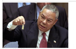 In the UN, Collin Powell holds a model vial of anthrax while arguing that Iraq is likely to possess WMDs